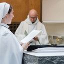 She stands at the altar to read her profession of vows.